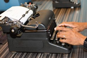 A person typing at the Story of the Day table