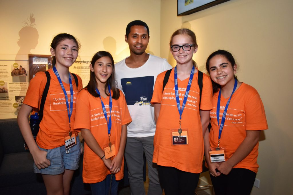 A group of students in oragne t-shirts at the American Writers Museum