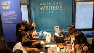 A classroom of students typing at the typewriters in the Story of the Day exhibit