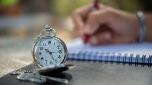 Open pocket watch and person writing