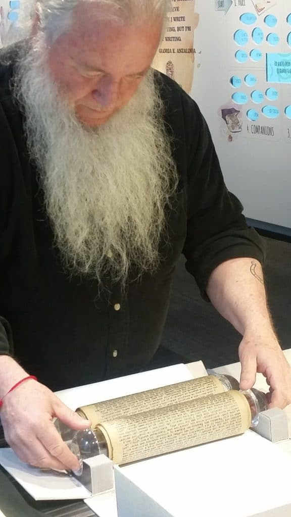 """A bearded man unrolls the """"On the Road"""" Scroll at the American Writers Museum"""
