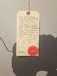 A luggage tag showcasing an immigration story of a visitor to the My America: Immigrant and Refugee Writers Today exhibit at the American Writers Museum in Chicago, IL