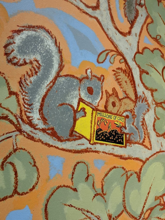 Three squirrels reading Millions of Cats by Wanda Gag in the mural in the Children's Gallery at the American Writers Museum in Chicago, IL.