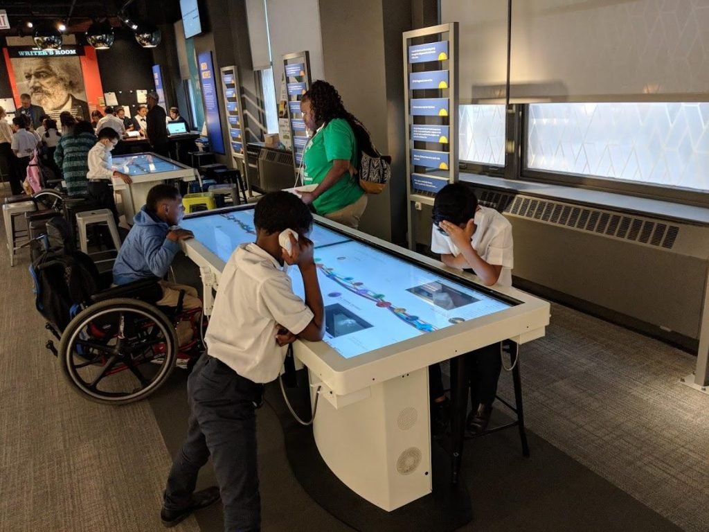 Students on a field trip interact with the Featured Works touch tables at the American Writers Museum in Chicago